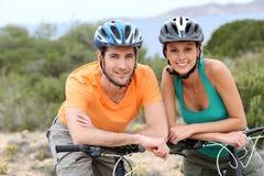 Portrait of happy couple riding bikes on island Stock Photography