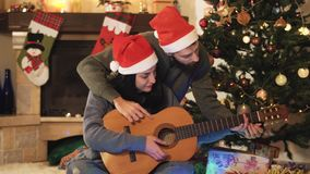 Portrait of happy couple in Santa`s hats on Christmas eve. Man teaching woman to play guitar. Christmas tree in the. Background. Family celebrating New Year stock video