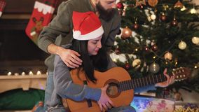 Portrait of happy couple in Santa`s hats on Christmas eve. Man teaching woman to play guitar. Christmas tree in the. Background. Family celebrating New Year stock footage