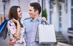 Portrait of happy couple with shopping bags in city smiling and huging. Happy couple with shopping bags after shopping in city smiling and huging stock photo