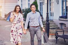 Portrait of happy couple with shopping bags in city smiling and huging. Happy couple with shopping bags after shopping in city smiling and huging royalty free stock photos