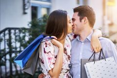 Portrait of happy couple with shopping bags in city smiling and huging. Happy couple with shopping bags after shopping in city smiling and huging royalty free stock images