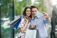 Portrait of happy couple with shopping bags in city smiling and huging. Happy couple with shopping bags after shopping in city smiling and huging stock photos
