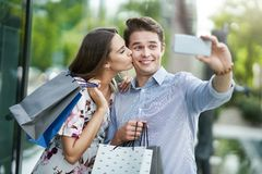 Portrait of happy couple with shopping bags in city smiling and huging. Happy couple with shopping bags after shopping in city smiling and huging stock photography