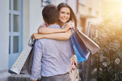 Portrait of happy couple with shopping bags in city smiling and huging. Happy couple with shopping bags after shopping in city smiling and huging stock images