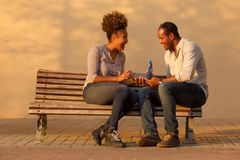 Portrait of happy couple sitting on bench with man giving anniversary gift. Full length portrait of happy couple sitting on bench with men giving anniversary Royalty Free Stock Image