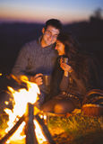 Portrait of the happy couple sitting by fire on autumn beach. At the night Royalty Free Stock Photos