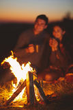 Portrait of the happy couple sitting by fire on autumn beach at Stock Photography