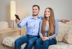 Portrait of happy couple sitting on sofa watching television together Stock Image