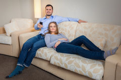 Portrait of happy couple sitting on sofa watching television together Royalty Free Stock Photography