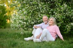 Happy couple sitting in spring park. Portrait of happy couple sitting in spring park royalty free stock images
