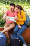 Portrait of happy couple sitting together looking at tourist map with luggage. Full length portrait of happy couple sitting together looking at tourist map with Royalty Free Stock Photo
