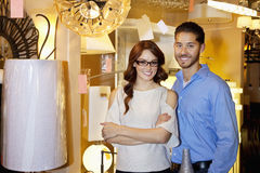 Portrait of a happy couple standing together in lights store Stock Images