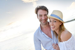 Portrait of happy couple in sunset walking on the beach Royalty Free Stock Photo
