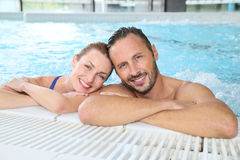 Portrait of happy couple in swimming pool relaxing Royalty Free Stock Images