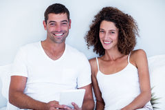 Portrait of happy couple using digital tablet on bed Stock Images