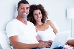 Portrait of happy couple using laptop on bed Stock Image