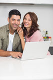 Portrait of a happy couple using laptop in kitchen Stock Photography