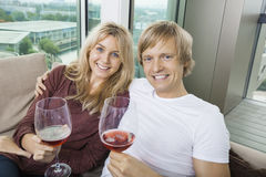 Portrait of happy couple with wine glasses in living room at home Royalty Free Stock Image