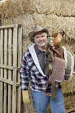 Portrait of happy cowboy carrying riding tack on shoulder Royalty Free Stock Images