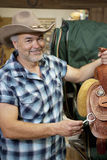 Portrait of a happy cowboy with riding tack in feed store Stock Images
