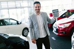 Portrait of happy customer buying new car. In salon royalty free stock photography