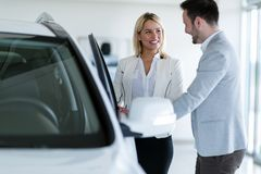 Portrait of happy customer buying new car. In salon stock photography