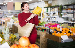 Portrait of happy customer selecting bananas in grocery Stock Photo