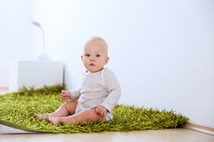 Portrait of a happy cute baby child at home interior. Stock Image