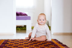 Portrait of a happy cute baby child at home interior. Stock Photography