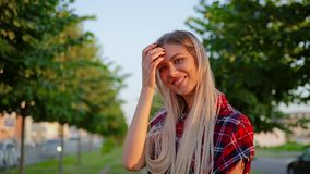 Portrait happy cute blonde girl in checkered red shirt straightens long gorgeous hair and smiles. With blurred background at alley with trees stock video