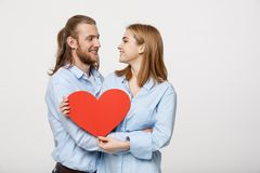 Portrait of happy cute couple in love enjoys Valentine`s Day. A man with a beard and a woman with blond short hair. Portrait of happy cute couple in love enjoys royalty free stock image