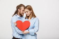 Portrait of happy cute couple in love enjoys Valentine`s Day. A man with a beard and a woman with blond short hair. Portrait of happy cute couple in love enjoys stock image