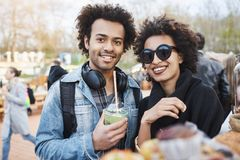 Portrait of happy cute dark-skinned couple with afro hairstyle, strolling on food festival, tasting and drinking. Cocktail. Two people in relationship on their stock image