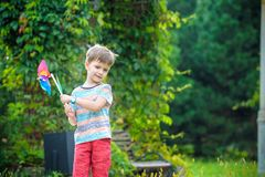 Portrait of a happy cute little boy holding pinwheel at the park. kid hold in hand play with windmill. boy smiling in spring or. Summer forest. Outdoors leisure royalty free stock photography