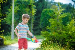 Portrait of a happy cute little boy holding pinwheel at the park. kid hold in hand play with windmill. boy smiling in spring or. Summer forest. Outdoors leisure stock photo