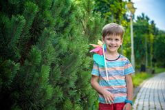 Portrait of a happy cute little boy holding pinwheel at the park. kid hold in hand play with windmill. boy smiling in spring or. Summer forest. Outdoors leisure royalty free stock image