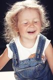 Portrait of a happy cute little girl in denim overalls, sitting in a studio on black background. Royalty Free Stock Photography