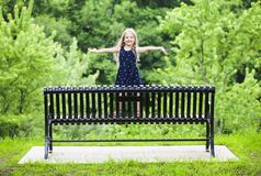 Portrait of happy little girl standing on metal bench in park stock photography