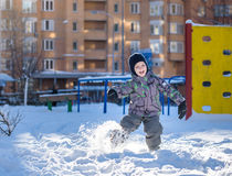Portrait of happy cute little kid boy in colorful warm winter fashion clothes. Funny child having fun in forest or park on cold da Royalty Free Stock Photo