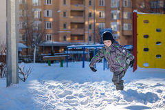 Portrait of happy cute little kid boy in colorful warm winter fashion clothes. Funny child having fun in forest or park on cold da Stock Image