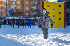 Portrait of happy cute little kid boy in colorful warm winter fashion clothes. Funny child having fun in forest or park on cold da Royalty Free Stock Photos