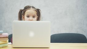 Portrait of happy cute smart girl sitting with stack of books and laptop at table, copy space. Education and development. Concept. Slow motions stock footage