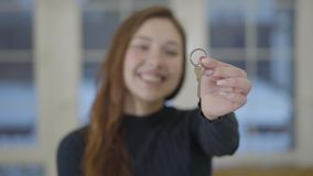 Portrait of a happy cute smiling woman showing the keys of a purchased new house or apartment to the camera. The focus. Portrait a happy cute smiling woman stock footage