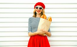 Cute smiling woman wearing red beret holding paper bag with long white bread baguette. Portrait happy cute smiling woman wearing red beret holding paper bag with stock image