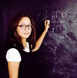 Portrait of happy cute student at blackboard in classroom smiling. Wearing hipster glasses Royalty Free Stock Images