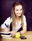 Portrait of happy cute student with book in classroom. Near blackboard Royalty Free Stock Photo