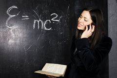 Portrait of happy cute student in classroom at blackboard back t Stock Photos