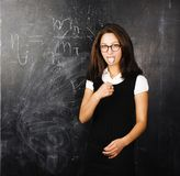 Portrait of happy cute student in classroom at blackboard back t Stock Image
