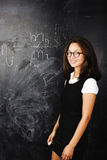 Portrait of happy cute student in classroom at blackboard back t Royalty Free Stock Images